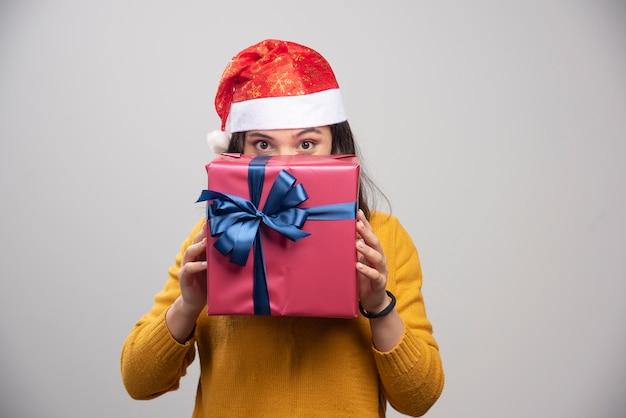 Glückliche frau in der weihnachtsmannmütze, die sich hinter geschenkbox versteckt.
