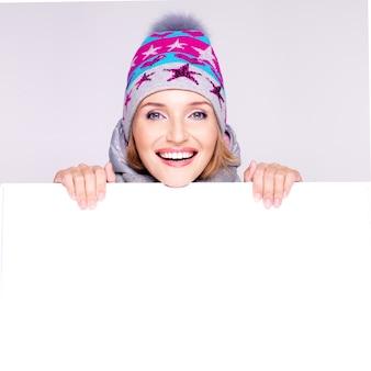 Glückliche frau in der winteroberbekleidung über weißem plakat in den händen