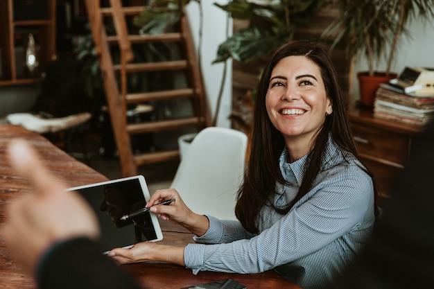 Glückliche frau in einem büro mit einem tablet-modell