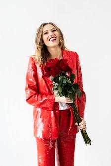 Glückliche frau in einem roten hosenanzug mit einem strauß rosen