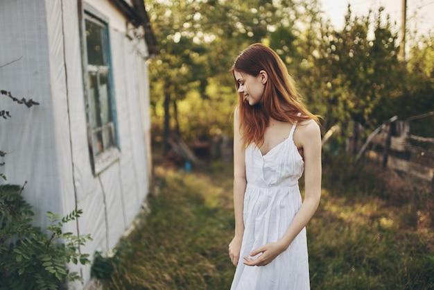 Glückliche frau in einem weißen sommerkleid nahe dem gebäude in der natur und den bäumen im hintergrund.