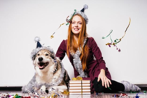 Glückliche frau in einer festlichen mütze sitzt neben einem hund auf einem geschenkhintergrund