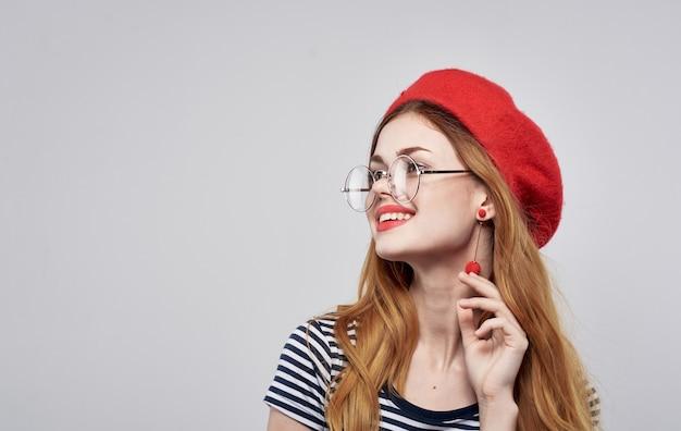 Glückliche frau in einer roten baskenmütze, die spaß auf einem lichtraum-nahaufnahme-kopierraum hat