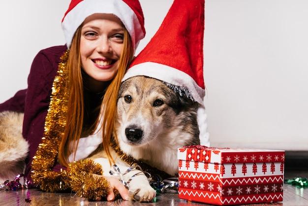 Glückliche frau in einer weihnachtsmütze umarmt einen hund auf einem geschenkhintergrund
