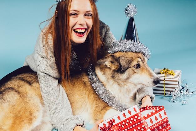 Glückliche frau in festlicher mütze sitzt neben großem hund auf geschenkhintergrund
