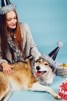 Glückliche frau in festlicher mütze sitzt neben großem hund