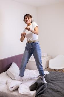 Glückliche frau in freizeitkleidung zu hause im schlafzimmer hört musik in kopfhörern, tanzt und springt