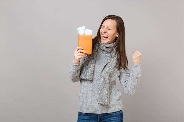 Glückliche frau in grauem pullover, schal mit geschlossenen augen, die gewinnergeste macht, halten pass-bordkarte einzeln auf grauem hintergrund. gesunde mode-lifestyle-leute-emotionen, konzept der kalten jahreszeit.