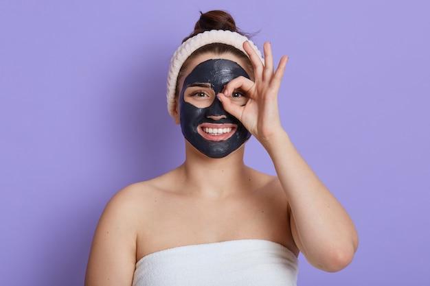 Glückliche frau in handtuch gewickelt und trägt haarband, das kosmetologische verfahren macht