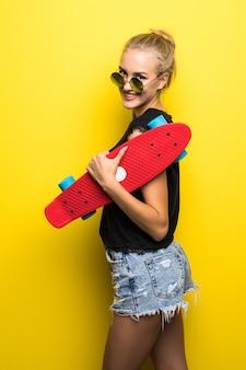 Glückliche frau in jeanskleidung und sonnenbrille mit skateboard, das spaß hat und die kamera über gelbem hintergrund betrachtet