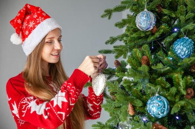 Glückliche frau in nikolausmütze schmücken weihnachtsbaum,