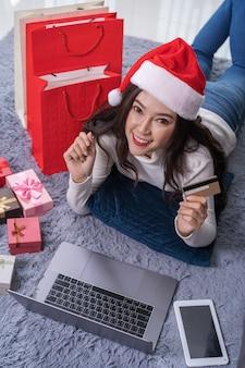 Glückliche frau in sankt-hut, der online für weihnachtsgeschenk mit laptop im wohnzimmer kauft