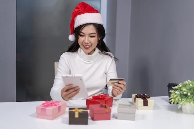 Glückliche frau in sankt-hut, der online für weihnachtsgeschenk mit tablette kauft
