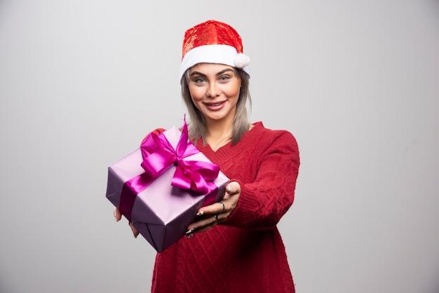Glückliche frau in sankt-hut, die weihnachtsgeschenk anbietet.
