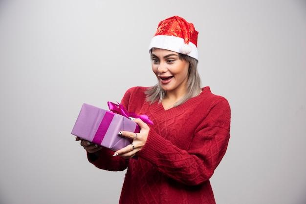 Glückliche frau in sankt-hut, die weihnachtsgeschenk betrachtet.