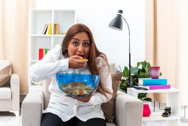 Glückliche frau in weißem hemd und schwarzer hose entspannt auf dem stuhl sitzend mit einer schüssel chips, die chips im hellen wohnzimmer isst