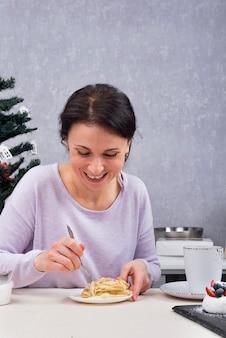 Glückliche frau isst in ihrer küche. frühstück mit dessert.