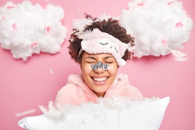 Glückliche frau kichert positiv hält augen geschlossen trägt nasenpflaster auf, um mitesser zu entfernen trägt schlafmaske und pyjama hält weiches kissen umgeben von fliegenden federn posen drinnen