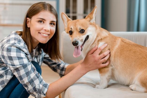 Glückliche frau lächelnd, während mit ihrem hund posierend