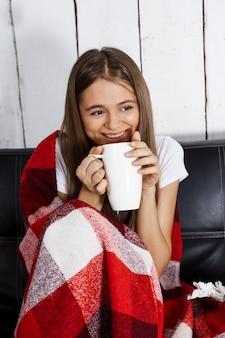 Glückliche frau lächelt, sieht fern, sitzt auf sofa zu hause.