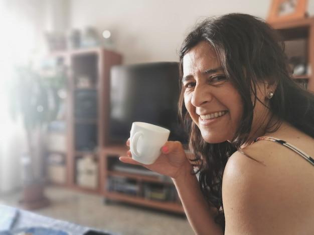 Glückliche frau lächelt und liegt mit einer tasse kaffee auf dem sofa