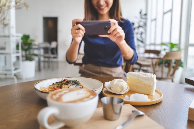 Glückliche frau machen fotos ihres lebensmittels im kaffeecaféshop in ihrem kühlenden feiertag