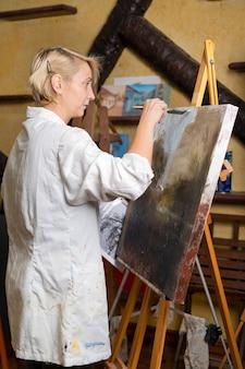 Glückliche frau malt auf leinwand mit dünnen pinsel-leinwand-ständern auf der staffelei-künstlerin zeichnet die staffelei-seitenansicht des weiblichen gemäldes auf leinwand im kunstheimstudio