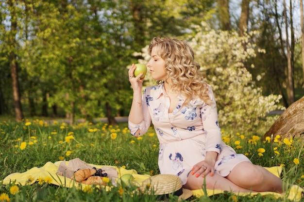 Glückliche frau mit apfel bei einem picknick im sommergarten