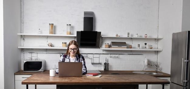 Glückliche frau mit brille, die am morgen zu hause arbeitet. mädchen, das kaffee trinkt. sie benutzt ihren laptop