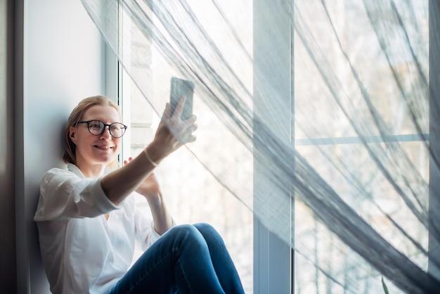Glückliche frau mit brille und weißem hemd sitzt auf dem fensterbretthintergrund und hält smartphone in der hand. süße blondine lächelt in die telefonkamera, nahaufnahme. online chatten.