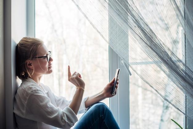 Glückliche frau mit brille und weißem hemd sitzt auf der fensterbank und hält smartphone in der hand. süße blondine lächelt in die telefonkamera, macht handgeste, nahaufnahme. online chatten.