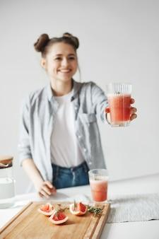 Glückliche frau mit brötchen lächelnd, das glas mit grapefruit-detox-smoothie zu jemandem streckt. weißer wandhintergrund. gesunde ernährung.