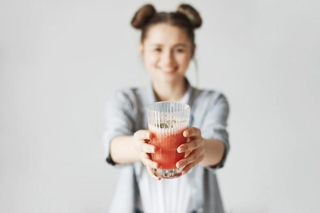 Glückliche frau mit brötchen lächelnd grapefruit detox smoothie über weiße wand strecken. gesunde ernährung. glas im fokus.