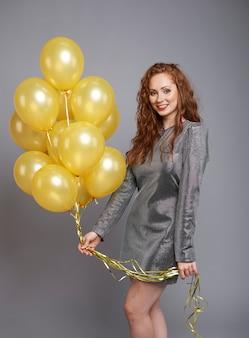 Glückliche frau mit bündel von luftballons