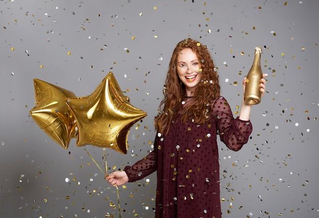 Glückliche frau mit champagner und sternförmigen luftballons