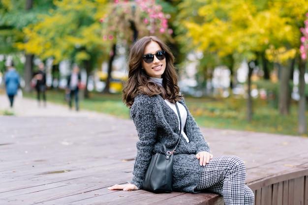 Glückliche frau mit charmantem lächeln und dunklem haar entspannt sich im herbstpark im sonnenlicht. sie sitzt auf dem holztisch und lacht im park mit gelben bäumen und büschen.