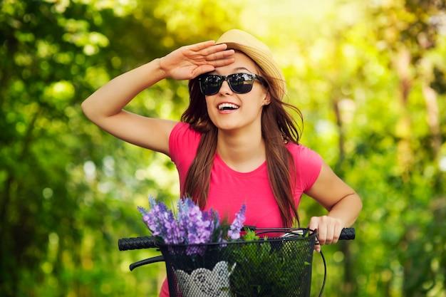 Glückliche frau mit dem fahrrad, das etwas beobachtet