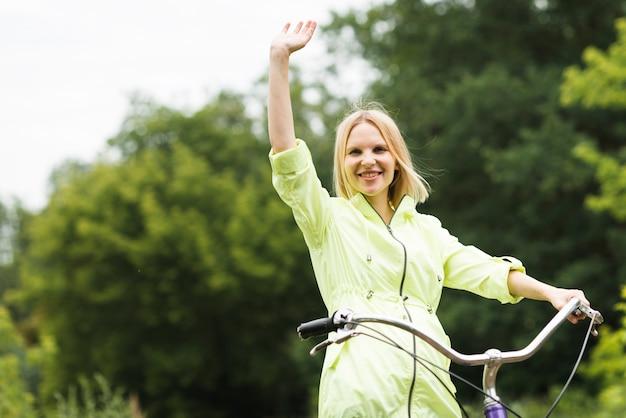 Glückliche frau mit dem fahrrad winken