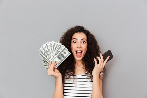 Glückliche frau mit dem gelockten haar, das fan von 100 dollarscheinen und von smartphone in den händen zeigen, dass sie unter verwendung des elektronischen geräts viel geld verdienen können