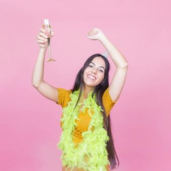 Glückliche frau mit dem getränk, das ihre arme beim tanzen auf rosa hintergrund anhebt