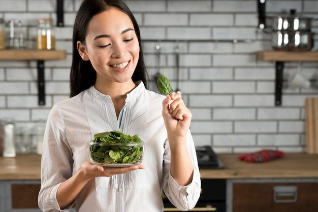 Glückliche frau mit dem halten des grünen basilikums treibt in der küche blätter