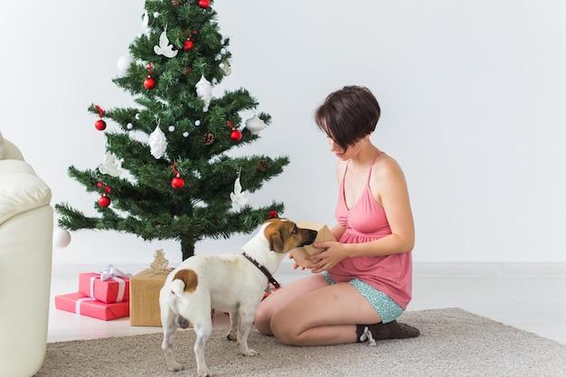 Glückliche frau mit dem hund, der weihnachtsgeschenke öffnet. weihnachtsbaum mit geschenken darunter. wohnzimmer eingerichtet.