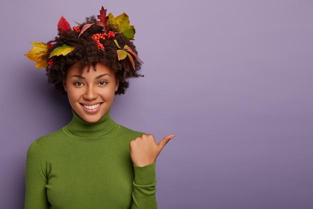 Glückliche frau mit dem lockigen haar, das durch herbstliche blätter verziert wird, stellt innen auf, zeigt daumen beiseite, gekleidet in grünen lässigen rollkragenpullover, lokalisiert über lila hintergrund, lächelt breit
