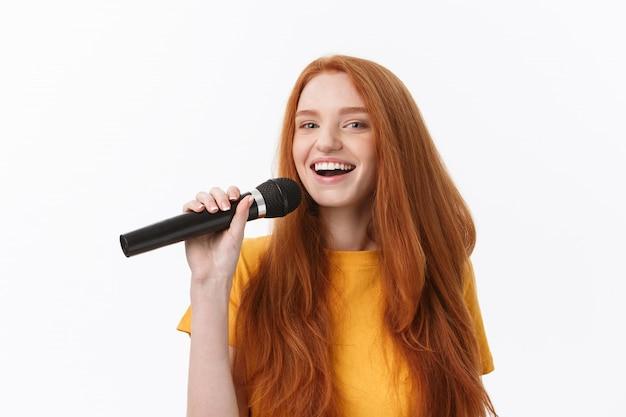 Glückliche frau mit dem lockigen haar, das singt, während mikrofon über weiß isoliert hält