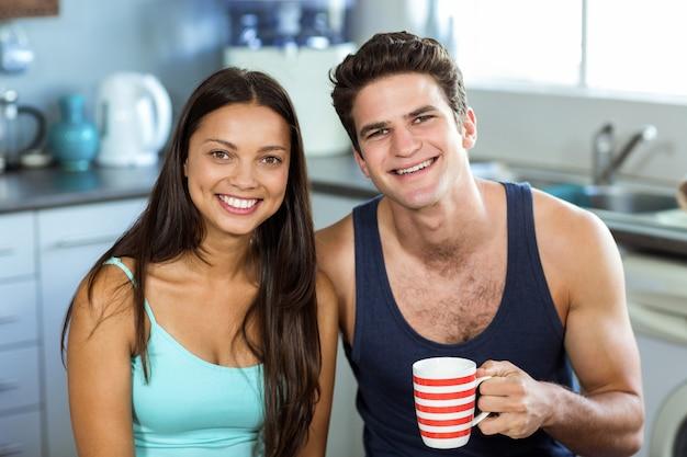 Glückliche frau mit dem mann, der zu hause kaffeetasse hält