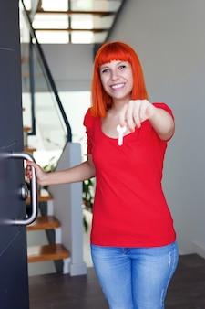 Glückliche frau mit dem roten haar, das ihr haus öffnet