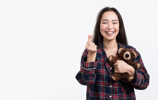 Glückliche frau mit dem teddybären, der herzzeichen zeigt
