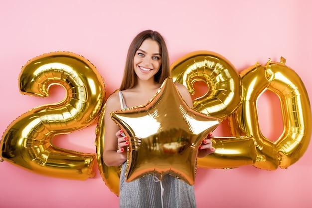 Glückliche frau mit den goldenen ballonen des neuen jahres 2020 lokalisiert über rosa