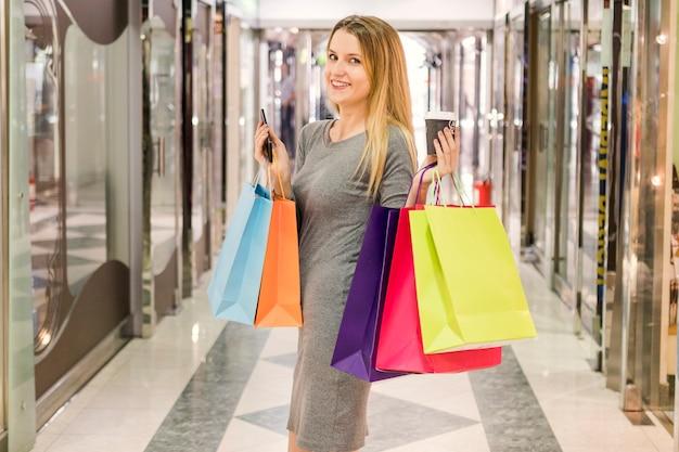 Glückliche frau mit den multi farbigen einkaufstaschen, die im mall stehen