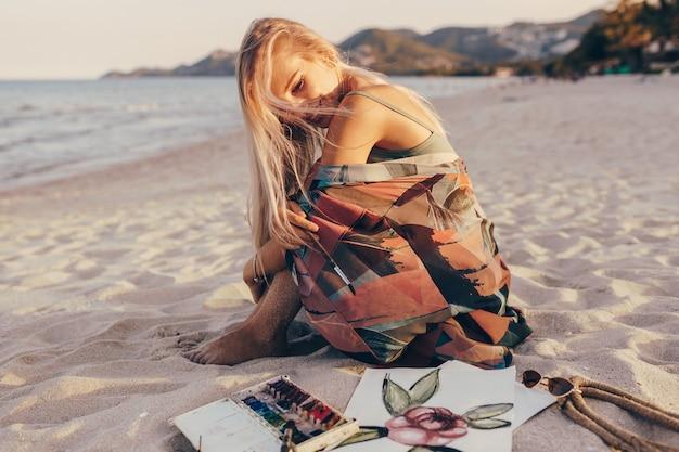 Glückliche frau mit den windigen blonden haaren, die auf sand sitzen und auf ihre aquarellkunst schauen